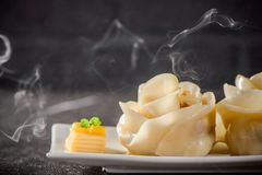 Rose flower shape dumpling on a white plate. On black background Royalty Free Stock Image