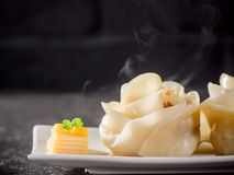 Rose flower shape dumpling on a white plate. On black background Stock Photography