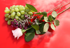 Rose, Flowers, Grapes. On red, a delicate arrangement of green grapes, a pale pink rose and small flowers Stock Images