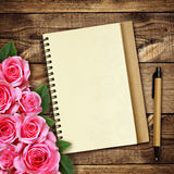 Rose flowers and a nonotebook with pen Stock Images