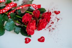 Rose flowers, red ribbon and decorative hearts on light wooden background royalty free stock photography