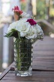 Rose flowers in vases, bottles and glasses. On the table Royalty Free Stock Images