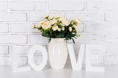Rose flowers and white wooden word love, over white brick wall Royalty Free Stock Photography