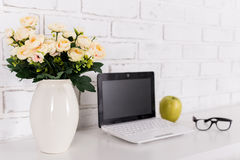 Rose flowers on workplace with modern laptop at home. Or in office royalty free stock photos
