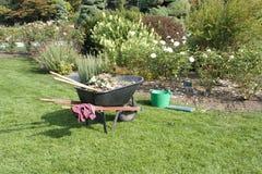 Rose garden and gardening tools Stock Photos