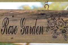 A rose-garden sign made of wood and hand painted. royalty free stock photos