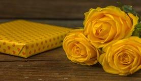 Rose gialle e contenitore di regalo su una vecchia tavola di legno Fotografia Stock Libera da Diritti