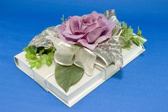 The Rose Gift Book. A book gift wrapped with a lace ribbon and purple rose on blue background Stock Image