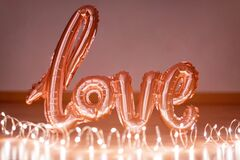 Rose gold foil balloon in the form of a word Love with light garland. Happy Valentine day. Word love letters from the inflatable