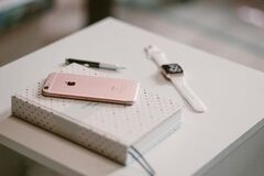 Rose Gold Iphone 6 S on Top of White Covered Book Stock Image