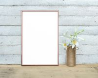 Free Rose Gold Vertical A4 Frame Mockup Near A Bouquet Of Lilies Stands On A Wooden Table On A Painted White Wooden Background. Rustic Royalty Free Stock Photos - 150665428