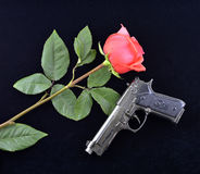 Rose and gun. Fresh rose and retro gun on black velvet stock photo