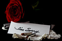 Rose with gun and sorry note Stock Images