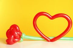 Rose and heart figures made of modelling balloons on table royalty free stock photo