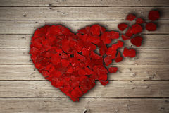Rose heart 3. Red rose petals arranged in shape of a broken heart on wooden table. Broken heart breakup concept separation and divorce icon. Symbol of medical Stock Images