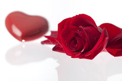 Rose and heart Valentines day.GN. Red valentins heart and a red rose laying on a glass surface.GN stock photo
