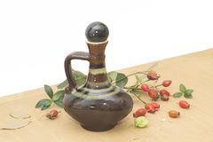 A rose hip branch and a brown ceramic vase. A rose hip branch and retro brown ceramic vase stock photography