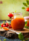 Rose hip jam. In jar with fresh berries and leaves royalty free stock photo