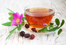 Rose hip tea. Cup of rose hip tea on a wooden background Stock Photography