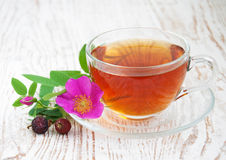 Rose hip tea. Cup of rose hip tea on a wooden background Royalty Free Stock Photography