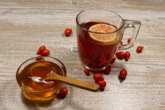 Rose hip tea with honey and lemon on wooden table. Rose hip tea with honey and lemon Stock Images