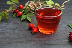 Rose hip tea with organic berry on black background Stock Photos