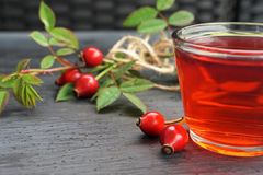 Rose hip tea with organic berry on black background royalty free stock images
