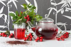 Rose hip tea. In teapot and tea glass with rose hip decorations Stock Photography