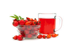 Rose hips and hawthorn berries and drink in a cup on a white bac Royalty Free Stock Photos