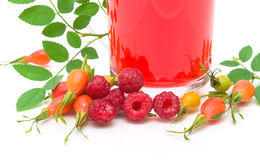 Rose hips, raspberries and fruit tea on a white background Stock Photos