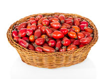 Rose hips in wicker basket isolated on white background. Stock Image