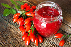 Rose jam. Jam with rose hips on wooden table Royalty Free Stock Photography