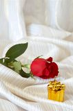 Rose and jewelry on bed Stock Image