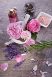Rose lavender spaPink English rose, lavender, organic salt and oil, spa wooden background. Rustic style Royalty Free Stock Images