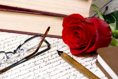 Rose Letter. A red rose lays on top of a hand written document with a pile of books behind royalty free stock images