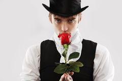 Rose and a man. Portrait of a young gentlemen wearing dinner jacket and black top hat. Shot in a studio Stock Photos