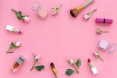 Rose, marco decorativo rosado de los cosméticos Barra de labios, bulto, sombreador de ojos y pequeñas flores color de rosa en cop imagen de archivo