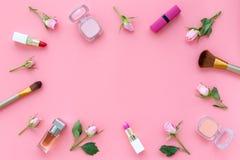 Rose, marco decorativo rosado de los cosméticos Barra de labios, bulto, sombreador de ojos y pequeñas flores color de rosa en cop fotos de archivo