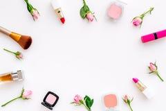 Rose, marco decorativo rosado de los cosméticos Barra de labios, bulto, sombreador de ojos y pequeñas flores color de rosa en la  fotos de archivo