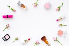 Rose, marco decorativo rosado de los cosméticos Barra de labios, bulto, sombreador de ojos y pequeñas flores color de rosa en la  imágenes de archivo libres de regalías