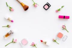 Rose, marco decorativo rosado de los cosméticos Barra de labios, bulto, sombreador de ojos y pequeñas flores color de rosa en la  imagen de archivo libre de regalías