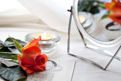 Rose and mirror. Beautiful red rose and burning candle near the mirror Stock Photo