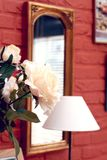 Rose and mirror. Still life with roses, mirror and a lamp, focus on the rose stock image