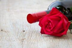 Rose mit Rotweinflasche auf hölzernem Valentinstag, anniversar Stockbilder