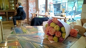 Rose multicolored bouquet on cafe table Royalty Free Stock Images