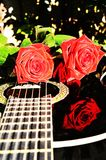 Rose on music, symbols. Roses on the strings of a guitar, with beautiful reflections on the object, suggesting love songs and desire for love stock image