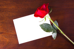 Rose note. A piece of paper on a wood desk with a red rose Stock Photo