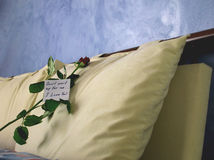 Rose with a note. Handwritten note, with a rose, resting on pillow Stock Photo