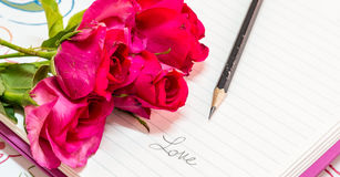 Rose and notebook. Rose on notebook and pencil with written love , Valentines concept Stock Photos