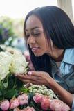 Rose odoranti della giovane donna afroamericana nel negozio di fiore fotografie stock